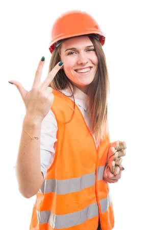 白で隔離された3本の指を持つ魅力的な幸せな女の子ビルダー 写真素材