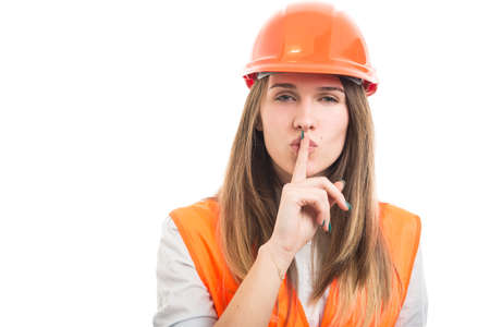 Young architech woman shushing with her finger to her lips or making gesture of silence Stock Photo