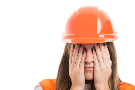 Portrait of scared woman engineer covering eyes with hands on white background with copy space Stock Photo