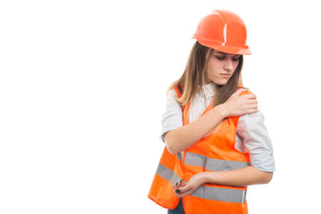 Engineer woman with hard hat got shoulder pain after work accident on white background with text space Standard-Bild