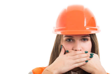 Young female constructor covering her mouth as speak no evil concept