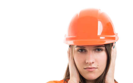 Closeup of woman builder in the hear no evil pose covering her ears on white background with text space