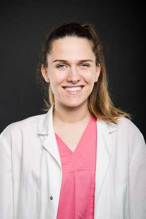 Young doctor portrait wearing robe and scrubs smiling on black background