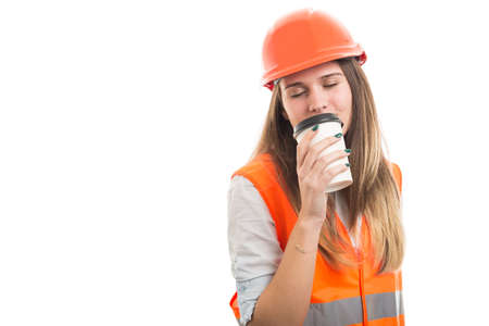 Beautiful woman engineer drinking coffee before work from disposable cup with advertising area Stock Photo