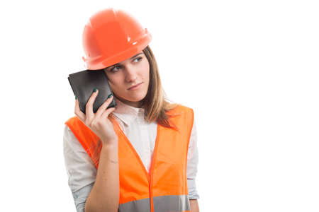 Thoughtful female architect holding leather wallet and making a plan to earn more money Stock Photo