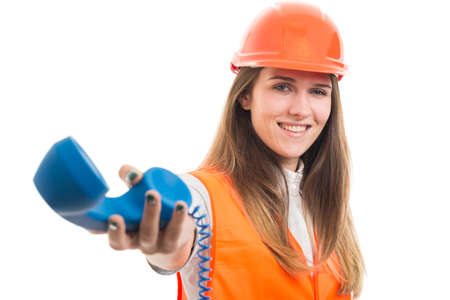 Successful female constructor giving the phone receiver to talk with a partner or customer