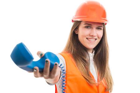 Succesvolle vrouwelijke constructor die de telefoonontvanger geeft om te praten met een partner of klant
