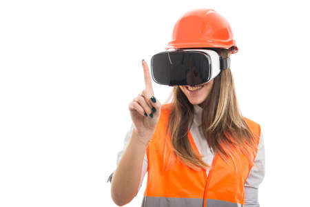 Female builder experiencing virtual reality thru modern glasses and pointing finger up