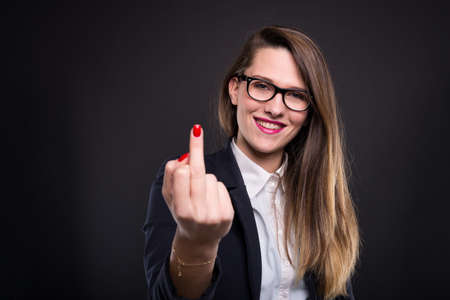 Rude funny manager rising middle finger and doing obscene gesture on dark background