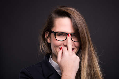 Business woman with glasses doing obscene sign and smiling on black background Standard-Bild