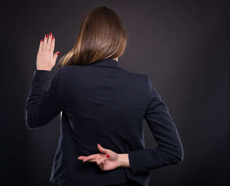 Businesswoman with crossed fingers behind her back making a false promise
