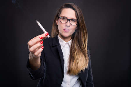 Relaxed businesswoman smoking and sharing a cigare with you on dark background
