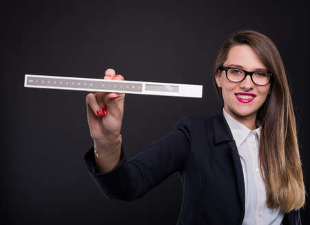 Young female entrepreneur showing measurement ruler and smiling at the camera