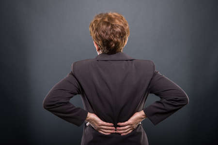 Business senior lady holding  her back like hurting on black background with copyspace advertising area Stock Photo