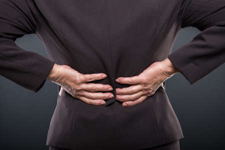 Close-up of business senior lady holding  her back like hurting on black background with copyspace advertising area