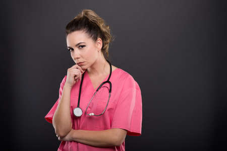 Portrait of lady doctor making thinking looking at camera  gesture on black background with copypsace advertising area Stock Photo