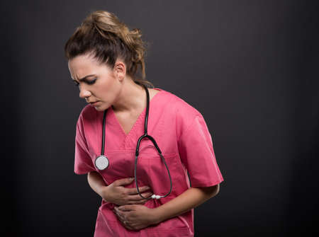 Portrait of beautiful young doctor holding stomach like hurting on black background with copyspace advertising area
