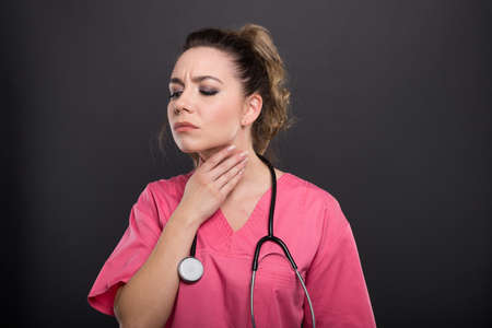 Portrait of beautiful young doctor having a throat ache on black background with copyspace advertising area