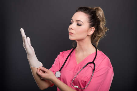 Portrait of beautiful young doctor putting on sterile gloves on black background