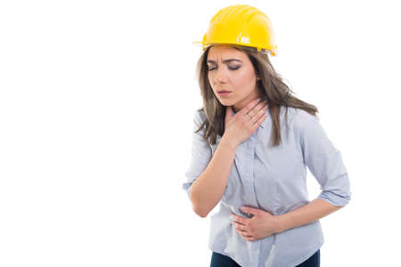 Female constructor holding her throat and stomach like hurting on white background with copypsace advertising area