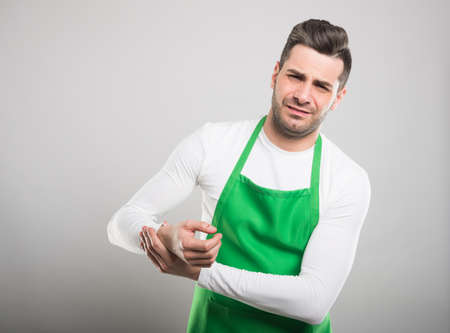 Good looking supermarket employer holding wrist like hurting on white background