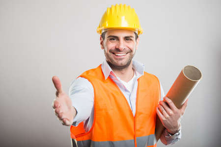 Portrait of young architect holding blueprints offering hand shake and smiling on gray background with copyspace advertising area