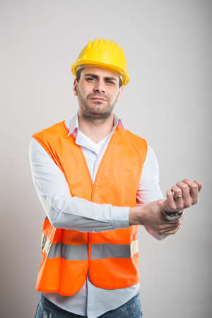 Portrait of attractive architect holding wrist like hurting on gray background with copyspace advertising area