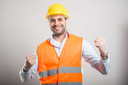 Portrait of young architect holding fists like fighting and smiling on gray background