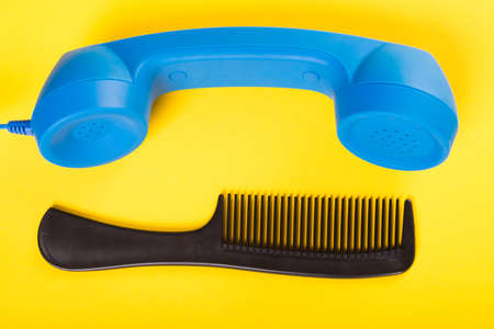Telephone receiver and one black comb on yellow  background