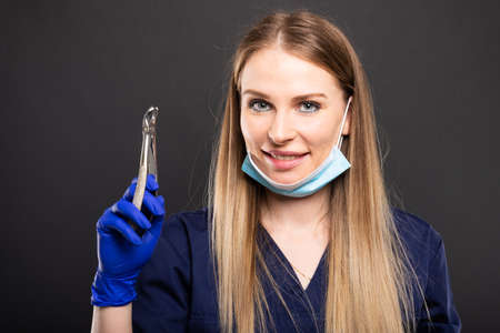 Beautiful female dentist using face mask holding tool and smiling on black background Stock Photo