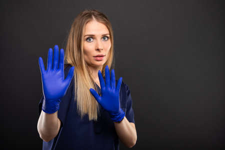 Female doctor wearing scrubs  making scared gesture on black background with copypsace advertising area