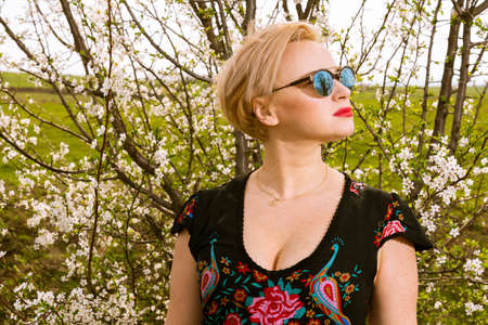 Portrait of fashionable blonde woman posing wearing shades outside on countryside background with copypsace advertising area