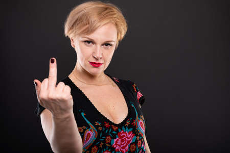 Portrait of cool fashionable woman showing middle finger gesture on black background with copypsace advertising area Banco de Imagens
