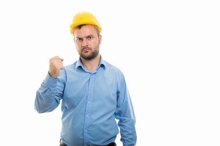 Portrait of young architect with yellow helmet showing angry fist gesture isolated on white background with copyspace advertising area Standard-Bild