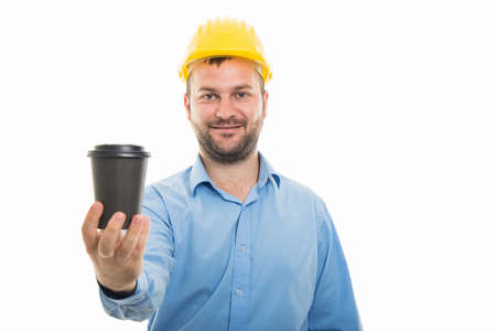 Portrait of young architect with yellow helmet holding to go coffee cup isolated on white background with copyspace advertising area Banco de Imagens