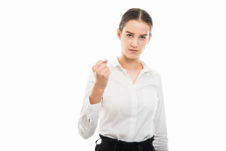 Portrait of young pretty bussines woman showing angry fist gesture isolated on white background with copyspace advertising area