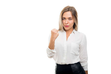 Young pretty business woman showing fist like fighting isolated on white background with copy space advertising area