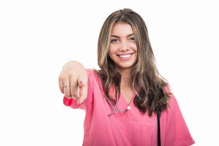 Portrait of beautiful young doctor wearing pink scrubs pointing camera isolated on white background with copy space advertising area