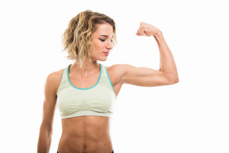 Portrait of fit girl showing her biceps isolated on white background with copy space advertising area