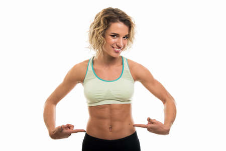 Portrait of fit girl showing her six pack isolated on white background with copy space advertising area