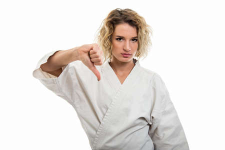 Portrait of young female wearing martial arts uniform showing dislike gesture isolated on white background