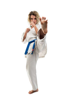 Female wearing martial arts uniform making karate move isolated on white background Reklamní fotografie - 116501622