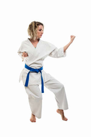 Full body of woman making martial arts pose wearing white outfit isolated on white background