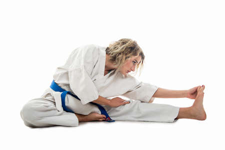 Full body of woman wearing martial arts outfit stretching muscles isolated on white background