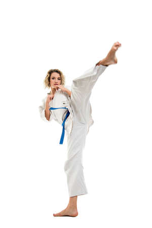 Full body of woman making martial arts kicking up wearing white outfit  isolated on white background