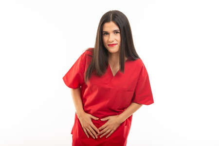 Portrait of nurse wearing scrubs making menstrual pain gesture isolated on white background with copy space advertising area