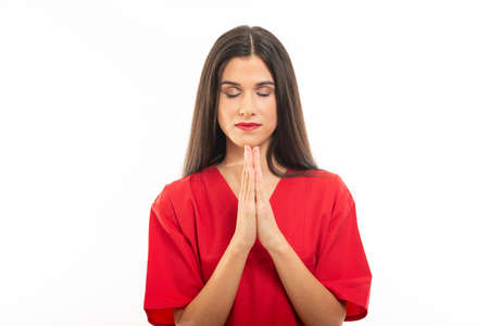 Portrait of beautiful nurse wearing scrubs making prayer gesture with eyes closed isolated on white background