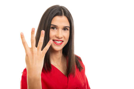 Portrait of beautiful nurse wearing red scrubs showing number four gesture isolated on white background with copy space advertising area