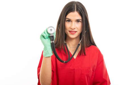 Portrait of beautiful nurse wearing scrubs putting stethoscope isolated on white background Stock Photo
