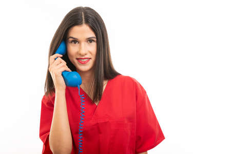 Portrait of beautiful young nurse wearing scrubs talking at phone receiver isolated on white background with copy space advertising area